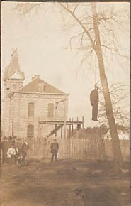 Unidentified corpse of African American male.  Gallows, courthouse-jail, and windmill in background.  Nine onlookers, two young boys.  1900-1915.  Location unknown.