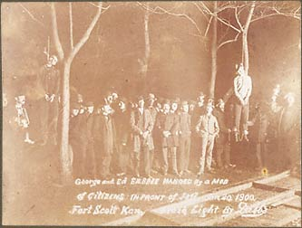 "The corpses of George and Ed Silsbee. January 20, 1900.  Fort Scott, Kansas.  A large group of spectators holding kerosene lamps, downed fence in foreground.   Gelatin silver print. Cabinet card. 7 x 10 in. Etched in negative, ""George and Ed SILSBEE HANGED by a MOB of CITIZENS IN FRONT OF JAIL. Jan. 20, 1900. Fort Scott Kan. Flash Light by Dabbs"""