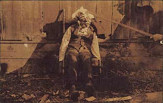 The bludgeoned body of an African American male, propped in a rocking chair, blood splattered clothes, white and dark paint applied to the face and head, shadow of man using rod to prop up the victims head. Circa 1900, location unknown.  Gelatin silver print. Real photo postcard, 5 3/8 X 2 7/8 in.